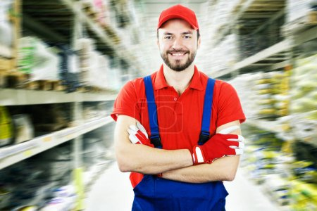 smiling warehouse worker standing between shelves