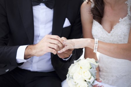Groom put the wedding ring on her bride