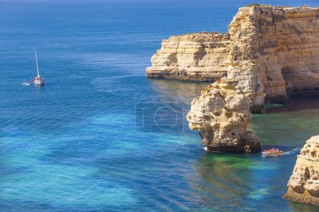 Boats with tourists visiting the caves at Marinha beach