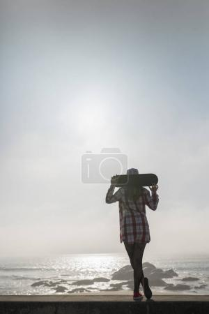 Silhouette of a girl holding a skateboard