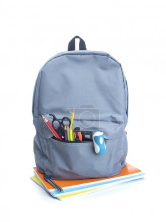 Backpack with school supplies on top of notebooks