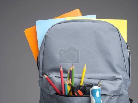 Photo pour Sac à dos avec fournitures scolaires sur fond gris - image libre de droit