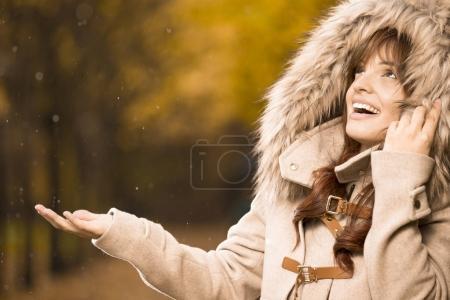 woman in autumn coat checking if it's raining