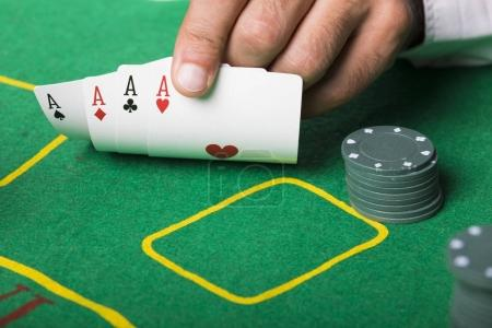 Poker player holding four aces cards