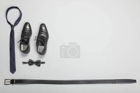 Bow, tie, shoes and belt on grey background. Happy Father's Day concept.