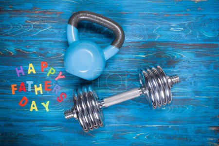 Happy Father's Day inscription with kettlebell and dumbbell on wooden table