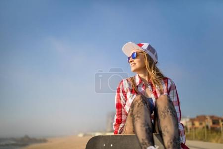 Cute girl sitting with skateboard near the beach and looking to the sea