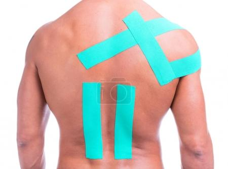 Back view of a muscular man with kinesio tape on the shoulder and back, isolated on a white background