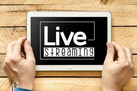 Photo pour Mains tenant la tablette avec live streaming mot sur la table en bois - image libre de droit