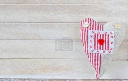 heart made of fabric on wooden background