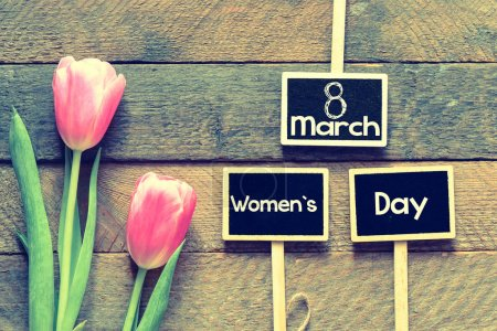 signboards with text 8 march women day and tulips on wooden background, international women day concept
