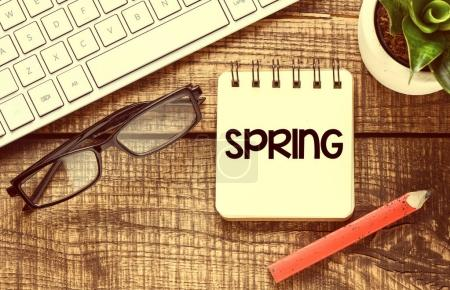 Spring on notepad on wooden background