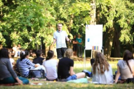 Photo pour Groupe d'étudiants assis dans le parc sur une herbe - image libre de droit