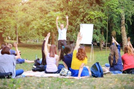 Un grupo de jóvenes estudiantes en el parque. Vista de un hombre gesticulando con las manos, de pie contra un grupo desenfocado de personas sentadas en la hierba .