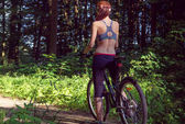 Girl cyclist on a mountain bike in a forest