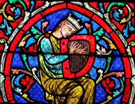 Photo for Stained glass window in the Notre Dame Cathedral in Paris, depicting King David playing on his Harp. - Royalty Free Image