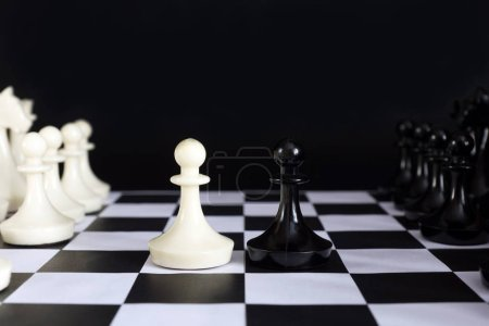 Start of chess game. Chess pieces against black background