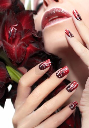 Red manicure with white wavy lines.