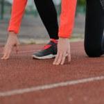 Blonde girl runner preparing for the start on the ...