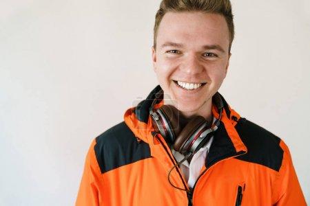 Photo pour Portrait d'un jeune homme souriant vêtu d'une veste orange et d'écouteurs sur fond clair. Bonne humeur et homme moderne . - image libre de droit
