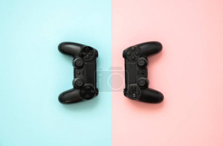 Photo for Game joystick console with electronics, accessories, pink and blue background. Exploration and technology. - Royalty Free Image