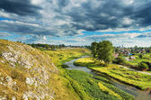 Summer rural landscape with river, rocks and clouds