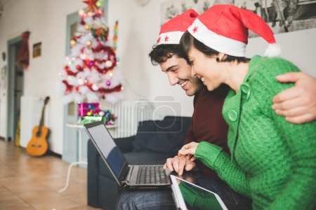 couple with santa claus hats on sofa