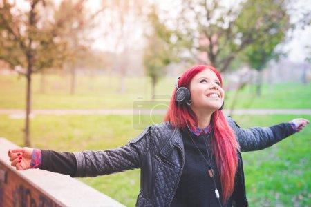 Photo pour Jeune belle cheveux roux venezuelan femme écouter de la musique souriant sentiment de plein air libre - musique, bonheur, concept de liberté - image libre de droit