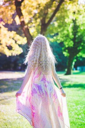 Photo pour Vue arrière du femme de jeunes beaux cheveux blonds portant robe rose debout dans la forêt - aventure, magie, rêve concept - image libre de droit