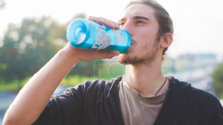 man relaxing after training drinking water