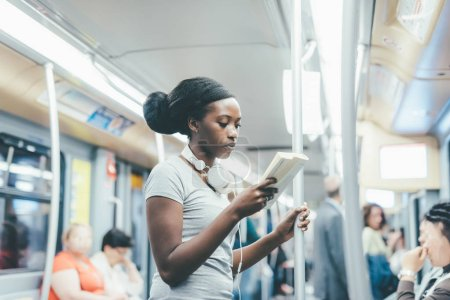 Woman traveling on subway reading book