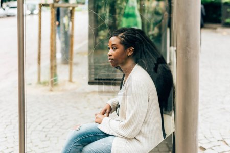 Woman sitting at the bus stop