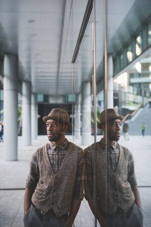 man leaning against mirrored wall overlooking