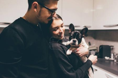 couple holding french bulldog puppy