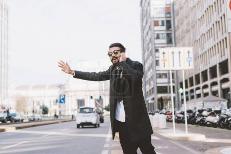 businessman asking taxi talking on smartphone
