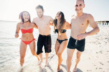 Photo pour Groupe d'amis milléniaux bras de marche autour sur le bord de la mer avoir du plaisir - amitié, interaction, concept de bonheur - image libre de droit