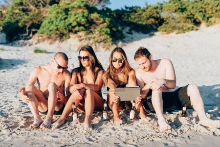 Photo pour Groupe d'amis millennials assis sur la plage avec tablette - sociale accro, phubbing, concept technologique - image libre de droit
