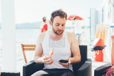 man using smartphone eating popsicle