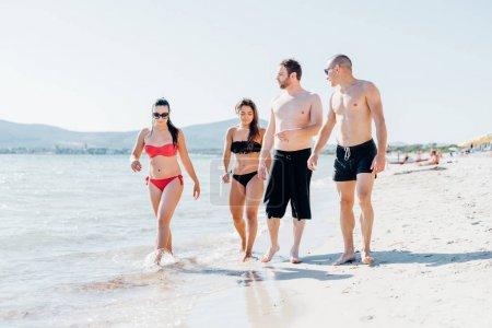 Friends walking on seashore having fun