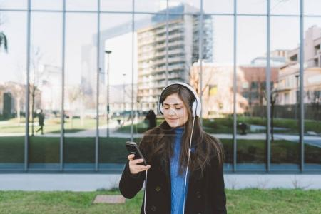 woman posing in city listening music