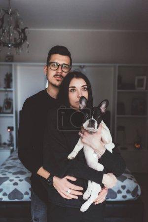 couple holding french bulldog