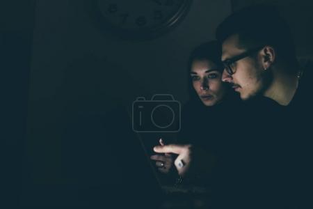 woman and man at darkness using computer