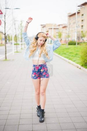 blonde girl listening music dancing