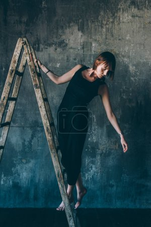 Photo pour Young beautiful woman indoor looking away posing on a ladder - model, fashion, influence concept - image libre de droit