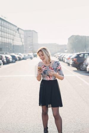Photo pour Jeune femme rétro-éclairage écoute musique en plein air sur smartphone rire - apprécier, bonheur, concept d'attitude - image libre de droit