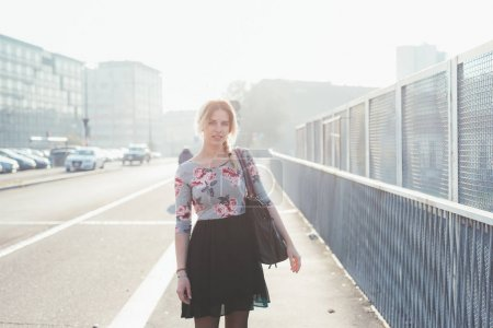 young woman outdoor back light posing looking camera - serene, positive emotions, confidence concept