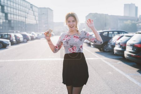 young woman outdoor back lit dancing listening music using smartphone - surprised, enjoying, happiness concept