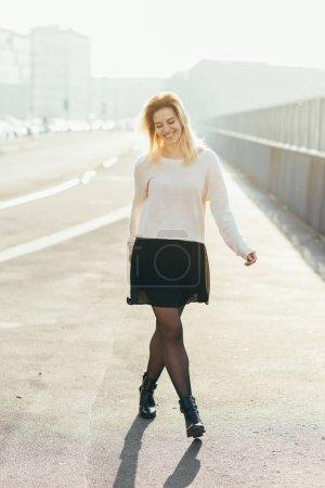 Photo pour Jeune femme marche arrière extérieure lumineuse s'amuser à la recherche de caméra - bonheur, serein, girl power concept - image libre de droit