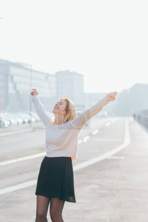young woman outdoor back light arms raised laughing - freedom, victory, satisfaction concept