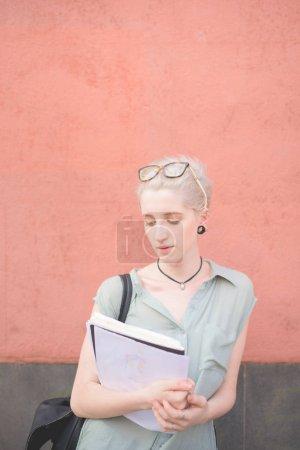 Foto de Mujer joven con libros al aire libre mirando lateral - estudiante, personas creativas, concepto no estereotipada - Imagen libre de derechos